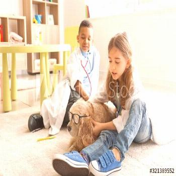 Cute little children dressed as doctors playing with dog at home ,