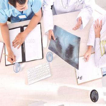 Doctors discussing x-ray of patient by DragonImages. General practitioner and his interns discussin