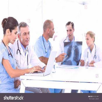 Doctors using computer whiles theirs colleagues looking at Xray in medical office ,
