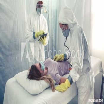 Doctors with bacteriological protection suits attending a patient ,