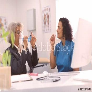 Female doctor teaching senior patient how to use inhaler in doctors office - Buy this stock photo a