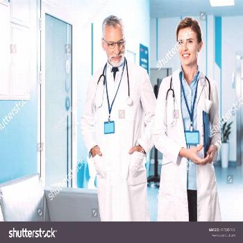 happy female and male doctors with badges and stethoscopes over neck walking in hospital corridor ,