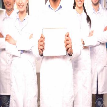 Team of young professional doctors in white coats standing together and holding blank sign Stock Ph