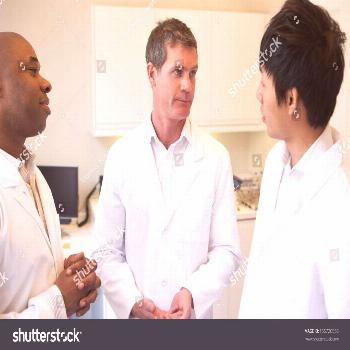 Three Doctors Having Discussion In American Hospital ,