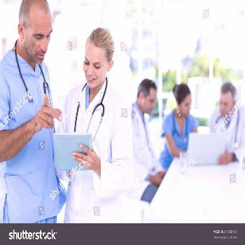Two doctors looking at clipboard while their colleagues working in medical office ,