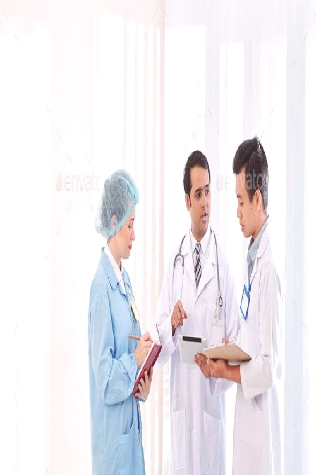 Doctor talking to colleagues by DragonImages. Serious doctors discussing article on tablet computer