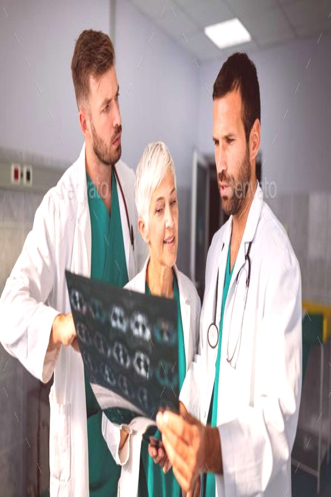 Doctors examining an x-ray report in hospital to make diagnosis by nd3000. Group of doctors examini