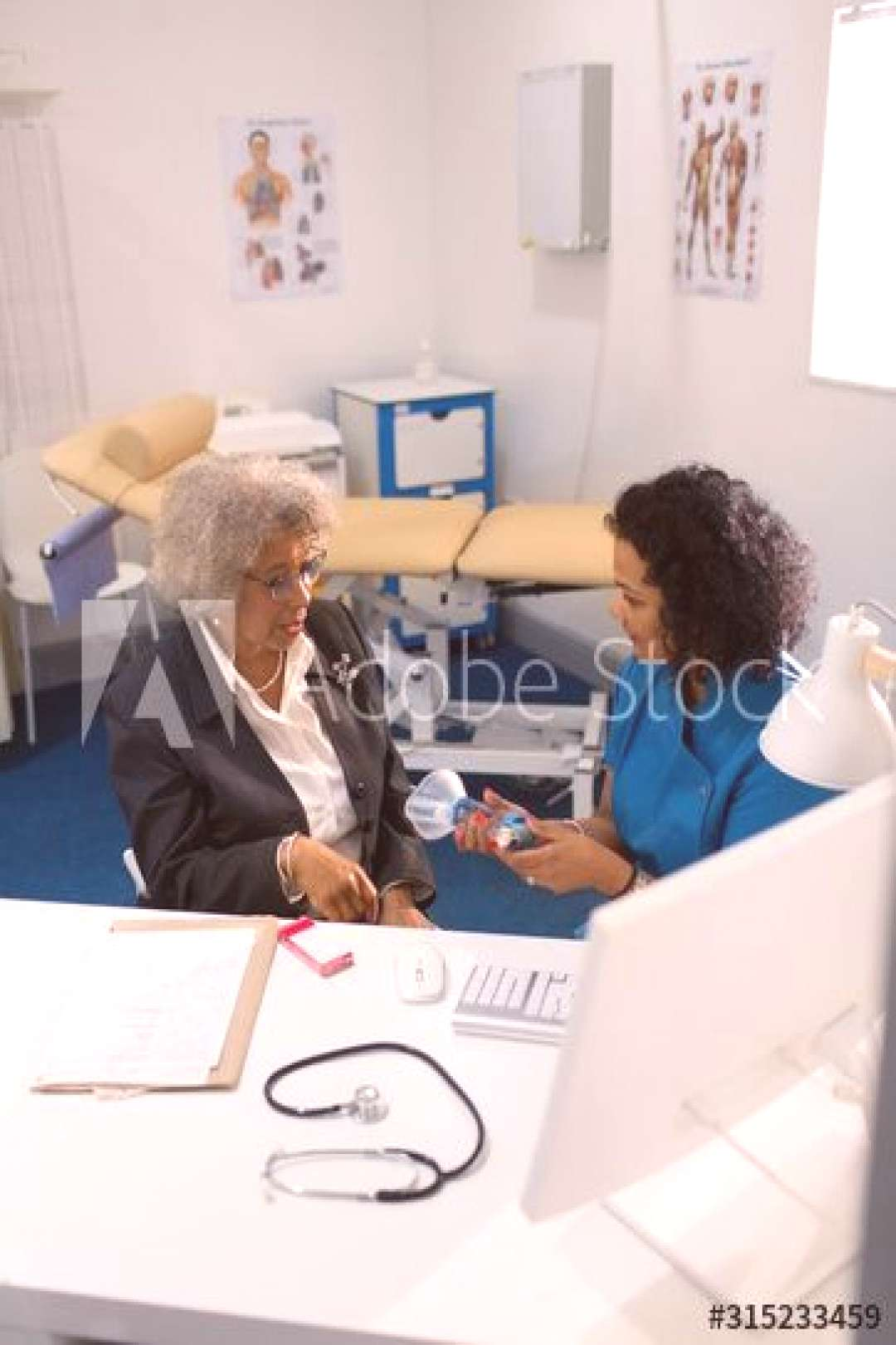 Female doctor teaching senior patient how to use inhaler in doctors office ,