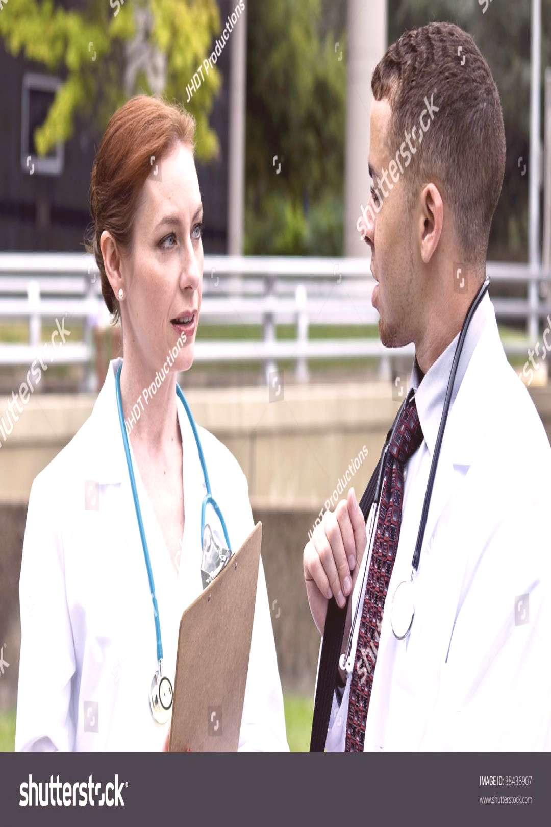 Two doctors on break in a city green space, engaged in friendly conversation. ,
