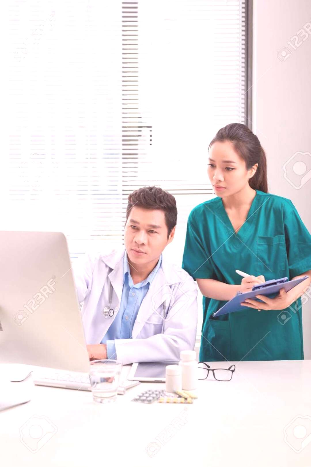 Two medical doctors consulting, smiling at office desk ,
