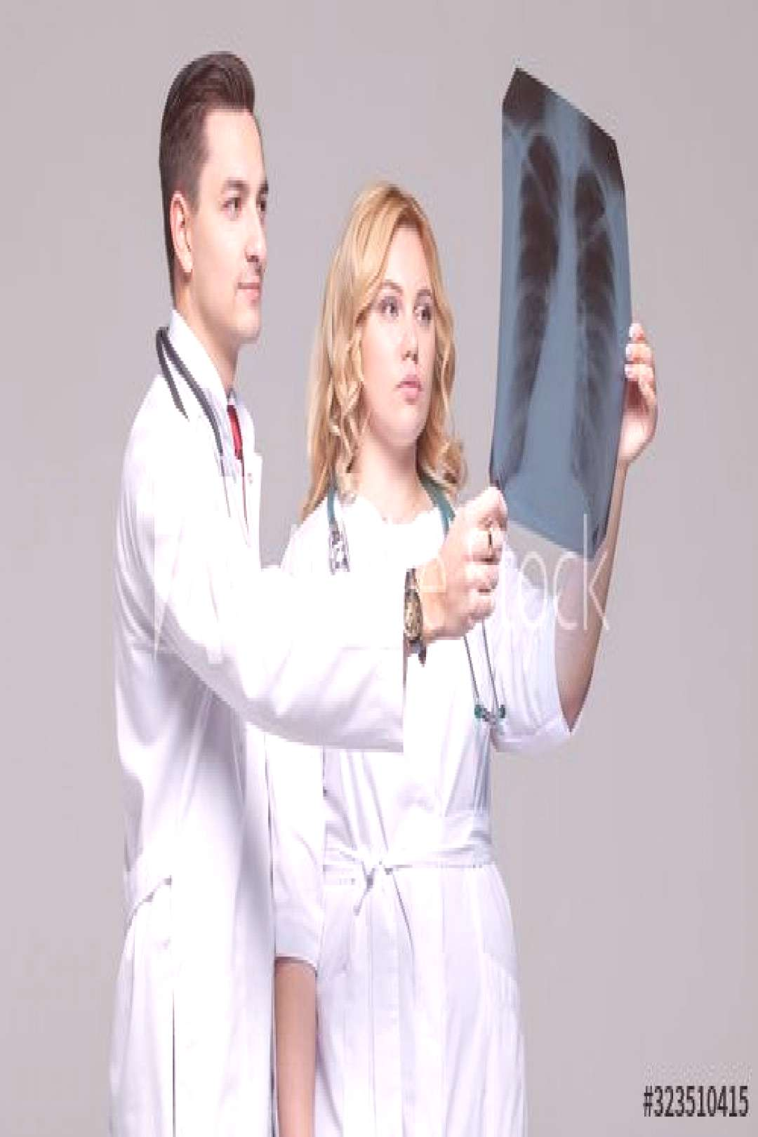 Two young doctors looking at the x-ray picture of lungs ,